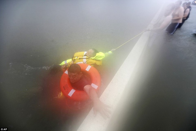 Lực lượng cứu hộ chạy đua với thời gian để giải cứu những người bị mắc kẹt do lũ lụt (Ảnh: AP)