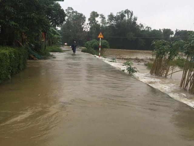 Người dân Thị xã Hương Trà bất chấp nguy hiểm lội qua đường tràn nước ở cạnh sông (ảnh: N.Phương)