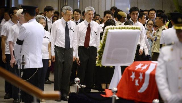 Thủ tướng Lý Hiển Long (giữa, cà vạt đen) đứng cạnh em trai Lý Hiển Dương (Ảnh: Straitstimes)