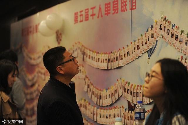Một thanh niên đang đọc thông tin về một cô gái độc thân tại sự kiện mai mối được tổ chức tại Bắc Kinh (Trung Quốc) ngày 9/4. Sự kiện này cũng thu hút hàng ngàn sinh viên các trường đại học danh tiếng ở Bắc Kinh như ĐH Bắc Kinh, ĐH Thanh Hoa, ĐH Nhân dân, ĐH Sư phạm Bắc Kinh và Học viện Khoa học Trung Quốc. (Ảnh: VCG)