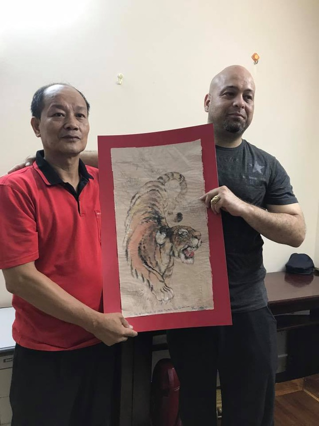 Võ sư Trần Lê Hoài Linh tiếp nhận tranh tặng của cao thủ Flores. Ảnh: DNĐ