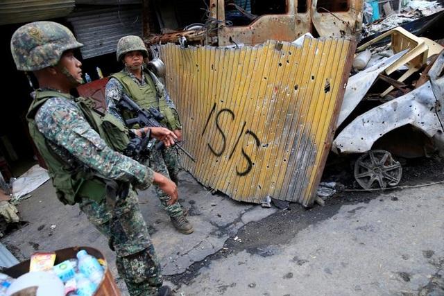 """Tính đến nay, cuộc giao tranh giữa quân đội chính phủ với các phiến quân thân IS tại thành phố Marawi trên đảo Mindanao miền nam Philippines đã bước sang tháng thứ 4. Có nhiều nhóm phiến quân tham gia vào cuộc giao tranh này, trong đó chủ yếu là các tay súng Maute. Trong ảnh: Các binh sĩ thuộc quân đội chính phủ đứng gác trước những căn nhà bị phá hủy tại Marawi. Họ đứng cạnh một tấm biển có ghi dòng chữ """"IS""""."""