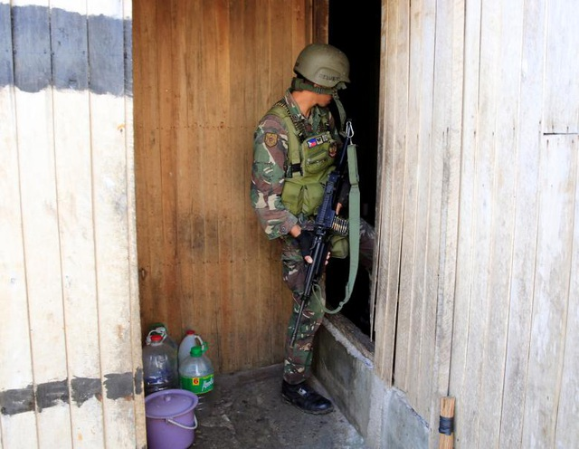 Binh sĩ quân đội Philippines cầm súng đột kích một căn nhà để truy lùng phiến quân Maute.
