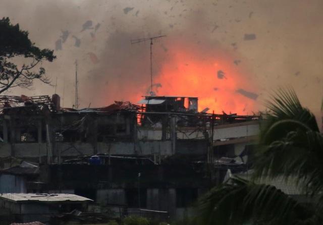 Tổng số người thiệt mạng trong các cuộc giao tranh khốc liệt giữa quân đội chính phủ và các phiến quân tại Marawi suốt 1 tháng qua lên tới 375 người, trong đó có 69 binh sĩ và 26 dân thường. Trong ảnh: Các mảnh vỡ và lửa bốc lên khi máy bay chiến đấu của quân đội Philippines thả bom xuống một khu vực nghi có phiến quân chiếm đóng ở Marawi.