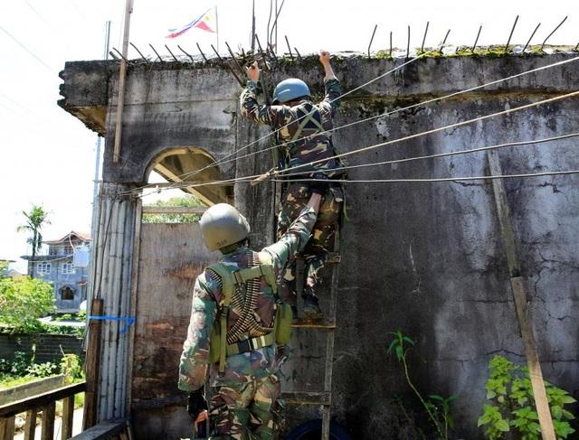 Theo người phát ngôn của Tổng thống Philippines, ông Ernesto Abella, các phần tử khủng bố vẫn đang tiếp tục sử dụng dân thường làm lá chắn sống và nhốt họ trong các nhà thờ Hồi giáo để đối đấu với quân đội chính phủ. Trong ảnh: Các binh sĩ Philippines trèo lên mái nhà để truy tìm dấu vết của các phiến quân khủng bố ở Marawi.