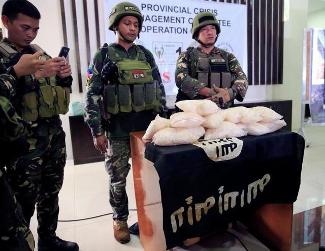 Quân đội Philippines cho biết hiện còn khoảng 100 phiến quân đang cố thủ tại Marawi. Trong ảnh: Các binh sĩ Philippines công bố tang vật gồm 11 kg ma túy đá, ước tính từ 2,2-5 triệu USD, và cờ của IS thu được từ các tay súng của nhóm phiến quân Maute.