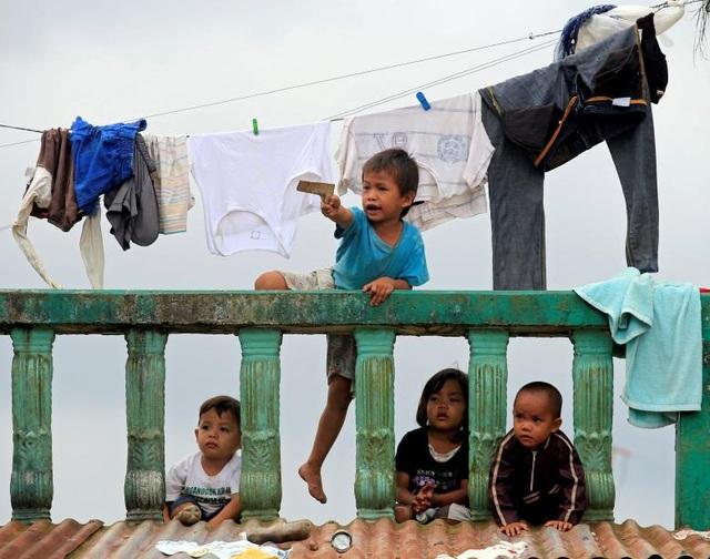 Nhiều trẻ em ở Marawi đã phải theo gia đình đi sơ tán và bỏ dở việc học ở trường. Trong khi đó, chính phủ Philippines hiện chưa đưa ra con số thống kê cuối cùng về thiệt hại cơ sở hạ tầng cũng như kinh tế ở Marawi. Trong ảnh: Một em nhỏ bắn súng đồ chơi tại một trung tâm sơ tán.