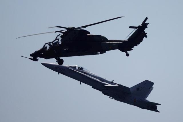 Máy bay chiến đấu McDonnel Douglas EF-18 Hornet (dưới) và trực thăng chiến đấu Eurocopter EC665 của Không quân Tây Ban Nha cùng nhau phô diễn các kỹ thuật nhào lộn trên không.