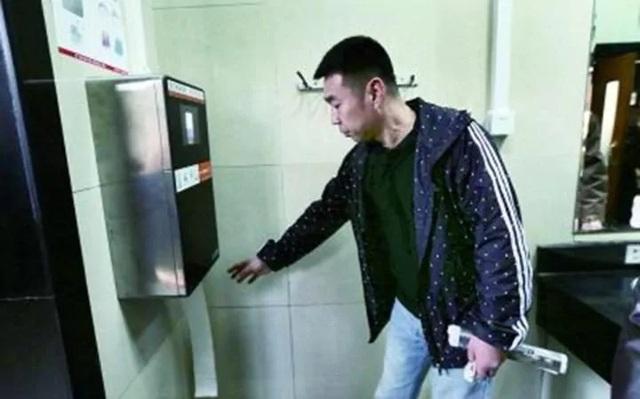 Một người dân trải nghiệm máy quét để lấy giấy vệ sinh (Ảnh: fawan.com)