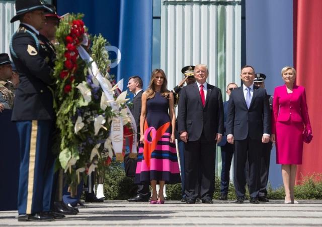 Tháp tùng Tổng thống Trump tham dự sự kiện ngoài trời tại Warsaw cùng Tổng thống Ba Lan Andrzej và phu nhân ngày 6/7, bà Melania mặc bộ váy dài không tay với gam màu hồng chủ đạo. Đệ nhất phu nhân Mỹ kết hợp đi cùng đôi giày màu hồng cho bộ trang phục này. (Ảnh: AFP)