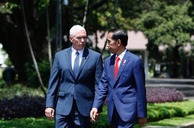 Ông Pence và ông Widodo trò chuyện khi đi cùng nhau trong khuôn viên dinh tổng thống ở Jakarta.