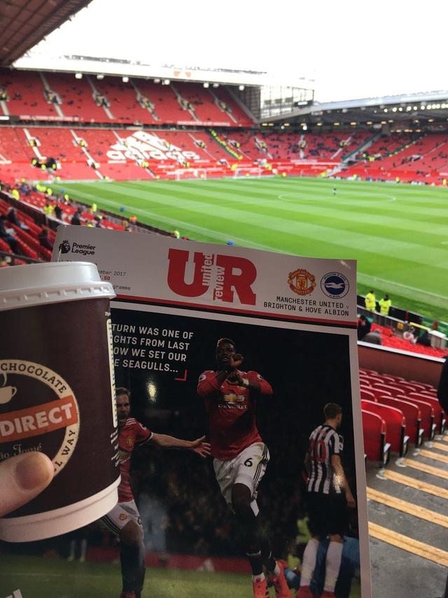 Một cổ động viên khoe quyển tạp chí của MU trước trận đấu gặp Brighton