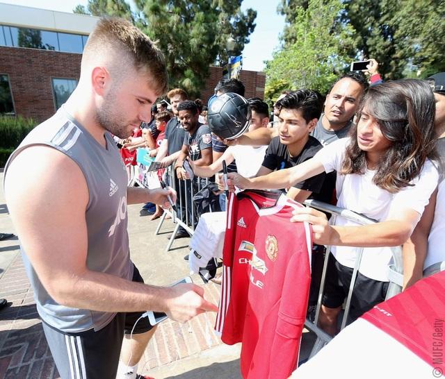 Hậu vệ trái Shaw ký tặng người hâm mộ bên ngoài sân tập của MU. Hậu vệ người Anh đang trong quá trình phục hồi chấn thương, anh vẫn chưa thể ra sân thi đấu cho Quỷ đỏ nhưng vẫn ở cùng đội
