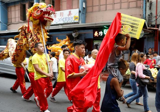 Những thanh thiếu niên đánh trống, múa lân trên đường phố ở khu phố của người Trung Quốc tại thủ đô Manila của Philippines. Múa lân là phong tục truyền thống thường có trong các dịp lễ, tết của người Trung Quốc. (Ảnh: Reuters)
