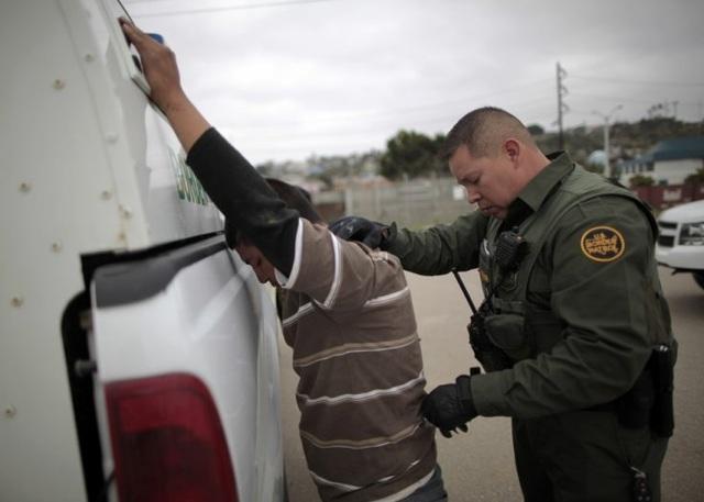 Lực lượng an ninh bắt giữ người nhập cư bất hợp pháp vào Mỹ (Ảnh: Reuters)