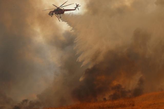Trực thăng xả nước từ trên cao để dập tắt đám cháy.
