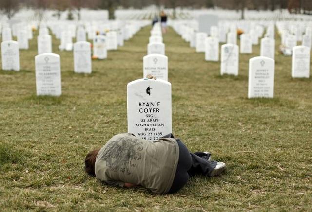 Theo thống kê của Viện Watson, Đại học Stanford, tổng số người chết trong cuộc chiến tại Afghanistan tính đến nay là 111.442 người, trong đó ngoài hơn 2.000 binh sĩ Mỹ và 1.136 binh sĩ đồng minh của Mỹ. Trong ảnh: Cô Lesleigh Coyer of Saginaw nằm trước mộ của anh trai, binh sĩ Ryan Coyer thiệt mạng khi tham chiến tại Afghanistan, tại nghĩa trang quốc gia Arlington ở bang Virgina, Mỹ.