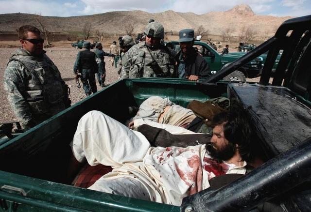 Trong tổng số hơn 111.000 người thiệt mạng trong cuộc chiến tại Afghanistan có 31.419 dân thường Afghanistan, 30.470 binh lính và cảnh sát Afghanistan, 42.100 phiến quân Taliban cùng các nhóm phiến quân khác, và 3.946 đối tượng khác như các phóng viên, nhân viên cứu hộ, các nhà thầu,… Trong ảnh: Các binh sĩ Mỹ và một cảnh sát Afghanistan đứng cạnh thi thể của các phiến quân Taliban sau vụ đấu súng gần ngôi làng Shajoy ở tỉnh Zabol năm 2008.