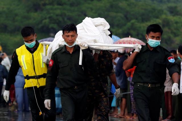 """""""Chúng tôi không nhận được bất kỳ thông tin nào về những người sống sót"""", Phyu Phyu Win, quan chức phụ trách cứu trợ và phúc lợi xã hội Myanmar, cho biết. Trong ảnh: Lực lượng tìm kiếm cứu hộ đưa thi thể nạn nhân được phát hiện trên biển vào bờ."""