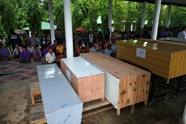 Ngoài thi thể các nạn nhân, lực lượng cứu hộ cũng tìm thấy một bánh máy bay, hai áo phao và một số túi chứa quần áo được cho là của nạn nhân vụ máy bay rơi. Trong ảnh: Quan tài của 10 nạn nhân trong vụ máy bay mất tích tại Myanmar.