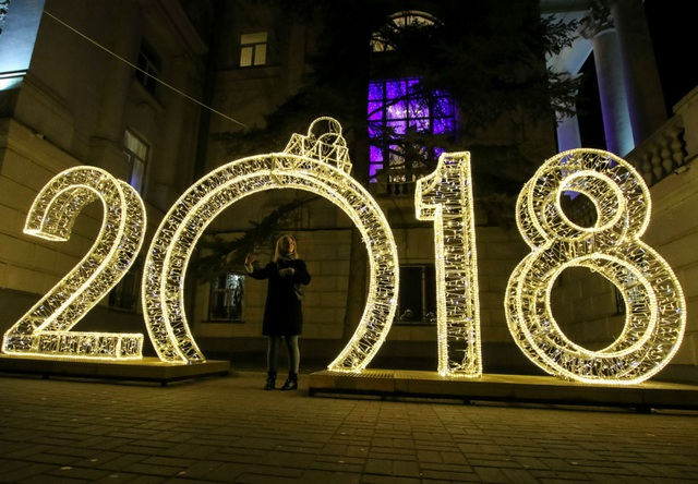 Một phụ nữ đứng gần khu vực trang trí được thiết kế cách điệu thành số 2018 để chào đón năm mới tại Sevastopol, Crimea - vùng lãnh thổ sáp nhập vào Nga từ năm 2014. (Ảnh: Reuters)