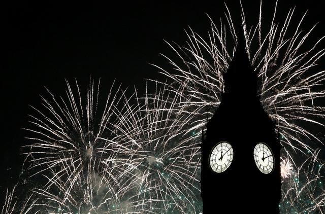 Người dân Anh tập trung tại khu vực đồng hồ Big Ben để được nghe tiếng chuông biểu tượng, đánh dấu thời khắc chuyển giao năm cũ và năm mới. (Ảnh: Reuters)