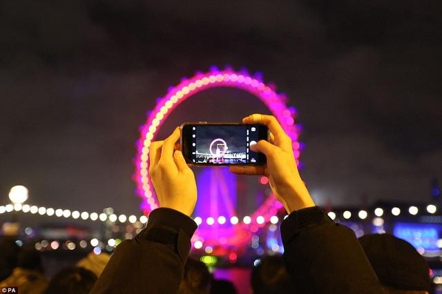 Một người sử dụng điện thoại để ghi lại hình ảnh vòng quay khổng lồ London Eye trong đêm giao thừa (Ảnh: PA)