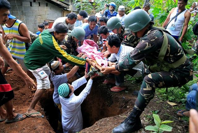 Giới chức Philippines cho biết ngoài hàng trăm phiến quân của nhóm Maute, đối đầu với quân đội chính phủ tại Marawi hiện nay còn có 40 tay súng nước ngoài tới yểm trợ. Các phiến quân thậm chí còn tích trữ lương thực cũng như vũ khí trong các nhà dân, nhà thờ, trường học cũng như mạng lưới đường hầm dưới lòng đất để chuẩn bị cho một cuộc chiến dài ngày. Trong ảnh: Các binh lính hỗ trợ người dân mai táng thi thể một nạn nhân thiệt mạng trong các cuộc giao tranh tại Marawi.