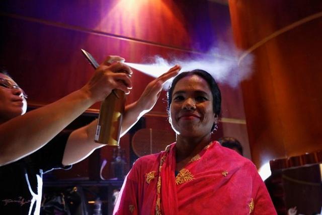 Một phụ nữ mỉm cười trong cánh gà khi được trang điểm trước khi bước lên sàn diễn.