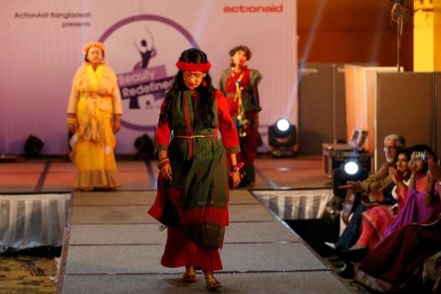 Các người mẫu bước đi trên sàn diễn trong tiếng vỗ tay của khán giả.