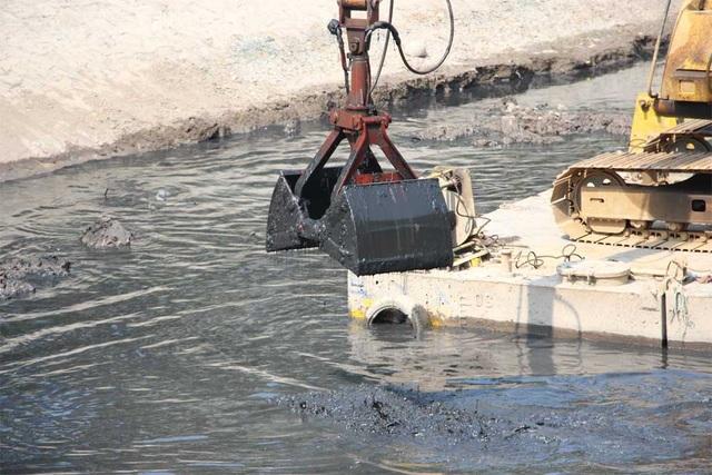 Máy múc cũng được huy động đến để đưa bùn từ lòng sông lên, nhằm khơi thông dòng chảy.