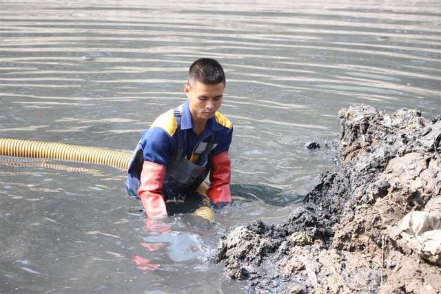 Người công nhân này làm nhiệm vụ điều khiển vòi hút để hút bùn từ lòng sông lên các xe bồn trên đường.