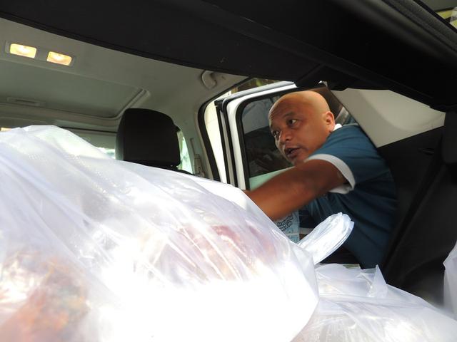 Ông Phạm Anh Tài chuyển các phần cơm lên xe để đưa đến các điểm thi phát cho học sinh