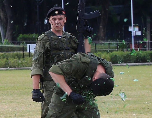 Một binh sĩ dùng đầu đập vỡ các chai thủy tinh, hoàn toàn không dùng đến các biện pháp bảo vệ (Ảnh: Reuters)