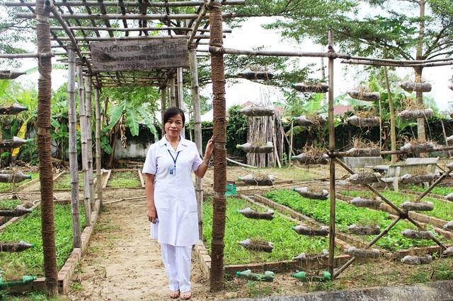Nữ bác sỹ chuyên khoa tâm thần Đinh Thị Hoan bên vườn rau liệu pháp chữa bệnh cho bệnh nhân tâm thần - Ảnh: Viết Hảo