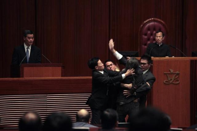 Các nhân viên an ninh chặn nghị sĩ Leung Kwok-hung tới gần cựu Trưởng Đặc khu hành chính Hong Kong Lương Chấn Anh (trái) tại Hội đồng lập pháp Hong Kong.