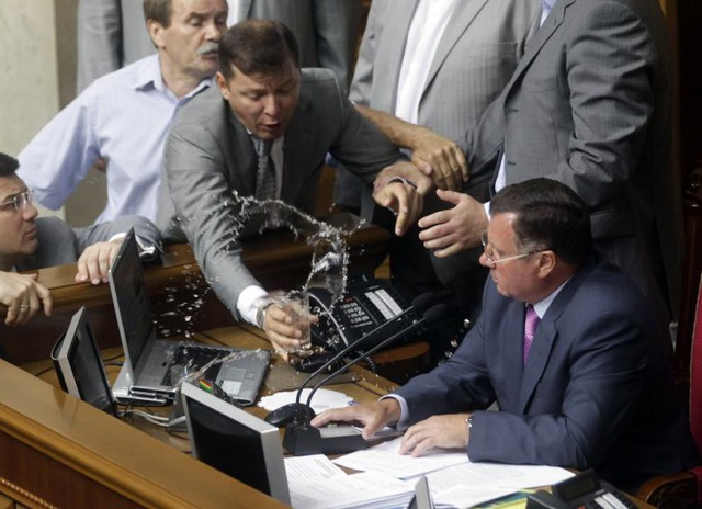 Nghị sĩ Oleg Lyashko (trái) đổ cốc nước vào người Phó Chủ tịch Quốc hội Ukraine Adam Martynyuk trong một phiên họp tại nghị trường ở Kiev.