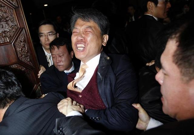 Nghị sĩ Kim Sun-dong (giữa) của đảng Lao động Dân chủ đã xô xát với các nhân viên an ninh sau khi ông ném bình hơi cay về phía ghế chủ tịch quốc hội để phản đối dự luật về thỏa thuận thương mại tự do với Mỹ tại tòa nhà Quốc hội ở Seoul, Hàn Quốc.