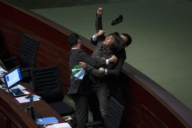 Nghị sĩ ủng hộ dân chủ Leung Kwok-hung ném đồ vật về phía người đứng đầu cơ quan tài chính Hong Kong John Tsang để yêu cầu một kế hoạch bảo vệ hưu trí toàn cầu trong phiên họp báo cáo ngân sách thường niên tại Hội đồng lập pháp Hong Kong.