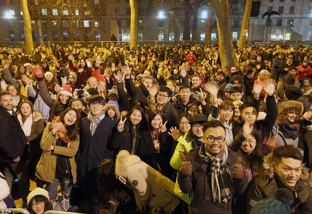 Nhiều người dân Anh cùng các bạn bè quốc tế háo hức chào đón màn bắn pháo hoa đặc sắc tại London. (Ảnh: PA)