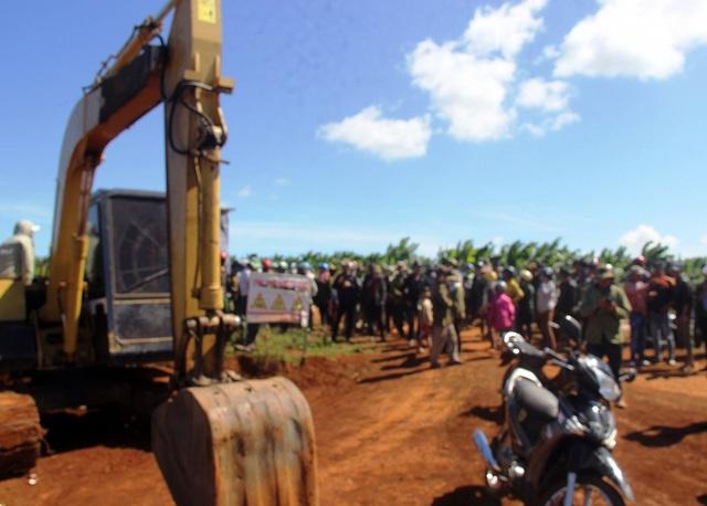Người vây quanh chiếc máy múc ngăn chặn không cho nhà thầu thi công