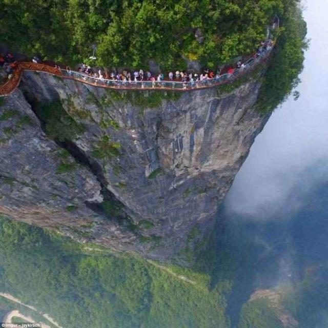 Hàng dài các du khách nối nhau đi bộ trên con đường chạy dọc theo sườn núi tại núi Thiên Môn ở Trương Gia Giới. Bên dưới chân là thung lũng thăm thẳm.