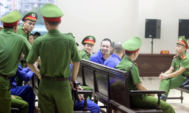 Nguyễn Văn Tình cười tươi, vẫy chào người thân và đồng phạm.