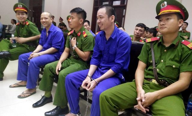 Nguyễn Văn Tình cùng 1 đồng phạm cười tươi trước khi phiên xử diễn ra.