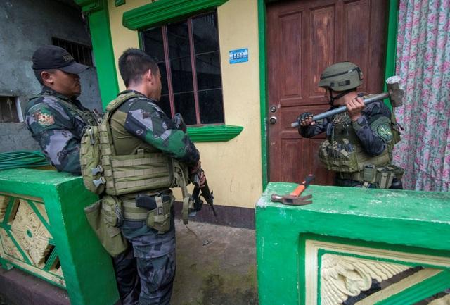 """""""Có những căn hầm và đường hầm mà thậm chí bom có sức công phá lớn cũng không thể phá hủy. Kể cả các phiến quân chiến đấu 2 tháng thì chúng vẫn không bị đói, tướng quân đội Carlito Galvez cho biết. Trong ảnh: Binh lính dùng các phương tiện hỗ trợ như búa để phá cửa một ngôi nhà nghi có phiến quân ẩn náu tại Marawi. (Ảnh: Reuters)"""