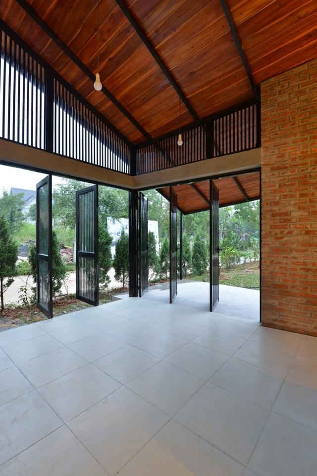 Các cánh cửa rộng và hệ lan dọc sát trần tạo cho căn nhà sự hòa hợp với thiên nhiên.