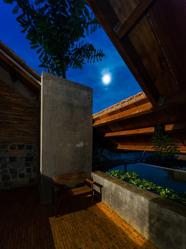 Có một không gian để ngắm trăng, hóng mát trong chính căn nhà của mình là ước mơ của bất cứ ai. Nếu như ban ngày, căn nhà mang vẻ đẹp bình yên, mềm mại nhưng không kém phần sang trọng, tiện nghi thì khi màn đêm buông xuống, căn nhà lại mang thêm một vẻ ảo diệu, đậm chất làng quê hơn. Ánh trăng hắt vào từng mảng trần mở, từng khung cửa sổ sẽ tạo nên những mảng sáng, mảng tối kì diệu cho cả căn nhà.