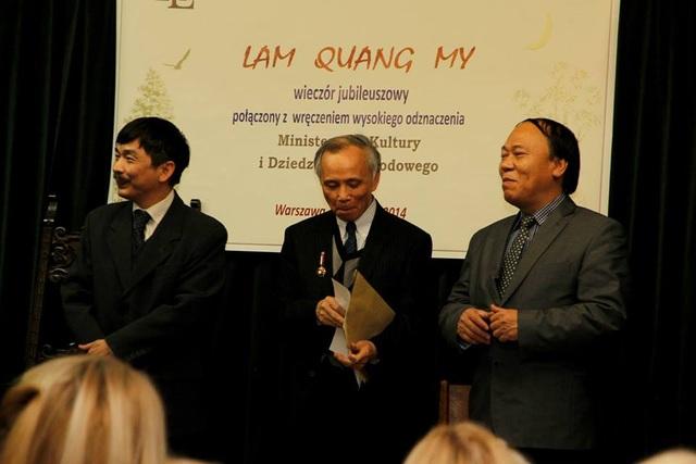 Nhà thơ Lâm Quang Mỹ (giữa) trong buổi lễ đón nhận Huân chương vì Sự nghiệp Văn Hoá do Bộ Văn Hoá và Bảo tồn Di tích Lịch sử Ba Lan trao tặng. Người bên trái là ông Ngô Hoàng Minh, thông dịch và dẫn chương trình. Người đứng bên phải là ông Lương Quang Chỉnh, Bí thư thứ nhất của ĐSQ Việt Nam tại Ba Lan.