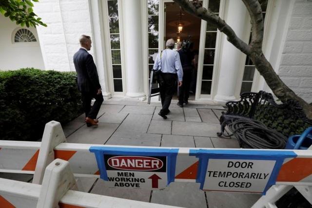 Mật vụ Mỹ theo sau các phóng viên đi qua các rào chắn để vào khu vực bên trong Nhà Trắng.