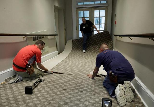 Các công nhân đặt thảm ở khu vực lối đi giữa các văn phòng tại Cánh Tây Nhà Trắng.